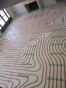 Serpentin de plancher chauffant sur dalles à plots dans une villa en construction